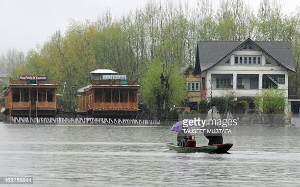 Kashmiri residents ferry a cooking gas cylinder in their boat as water levels rise on Dal Lake in Srinagar on April 1 2015 Many low lying areas in...