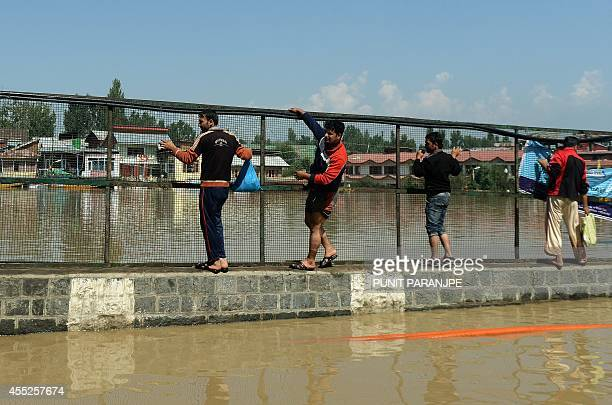 Kashmiri residents negoatiate a walled fence to avoid water on the flooded banks of Dal Lake in Srinagar on September 11 2014 The floods and...