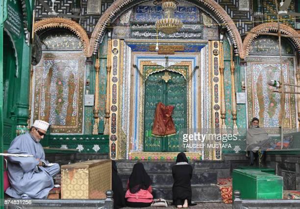 Kashmiri residents pray at the door to the KhankaheMoula at the Sayyid Ali Hamadani shrine in Srinagar on November 16 2017 A thunderbolt struck the...
