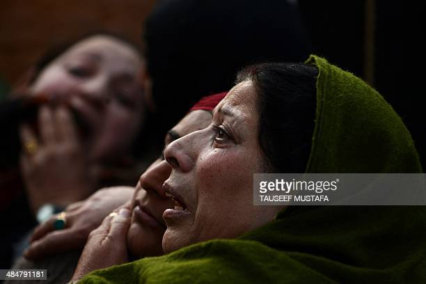 Kashmiri residents react and cry at the scene of their gutted house where Indian troops killed two militants in the outskirts of Srinagar on April 14...
