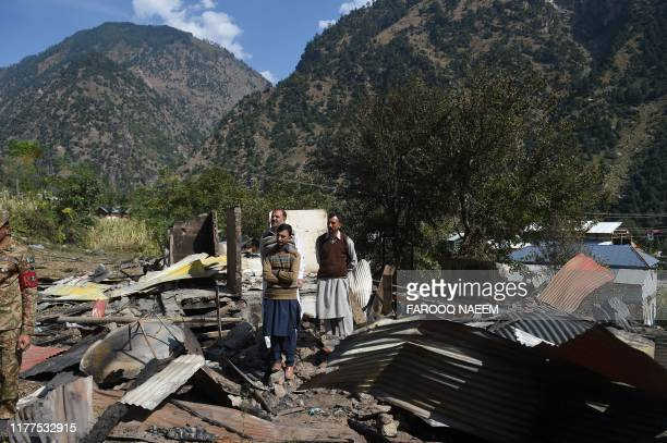 Kashmiri residents stand on the wreckage of a destroyed house after cross border shelling in Jura a village of Neelum valley in Pakistanadministered...