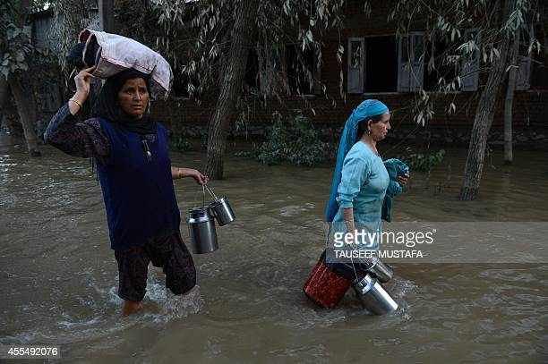 Kashmiri residents wade through floodwaters in Rakshalana south of Srinagar on September 15 2014 Rescuers struggled to reach more than 200000 people...