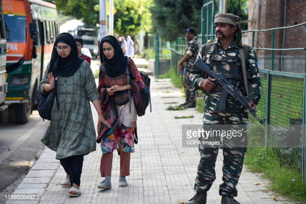 Kashmiri residents walk next to Indian Troops standing on guard as Additional Indian Troops arrive in Srinagar Fear and confusion have gripped...