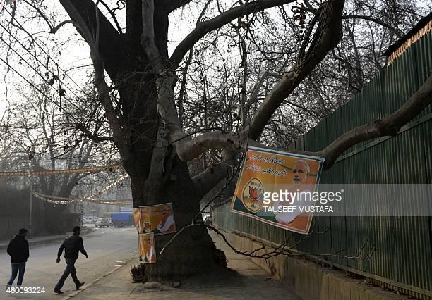 Kashmiri residents walk past a banner bearing the image of Bharatiya Janata Party leader and Indian Prime Minister Narendra Modi in Srinagar on...
