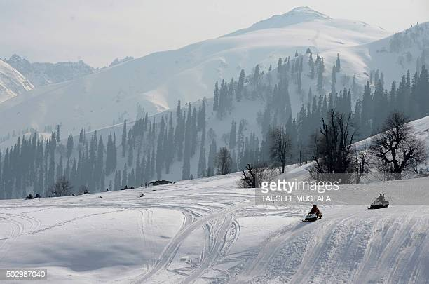 A Kashmiri rides a snow scooter carrying tourists in Gulmarg about 55 kms north of Srinagar on December 31 2015 Gulmarg is the main ski destination...