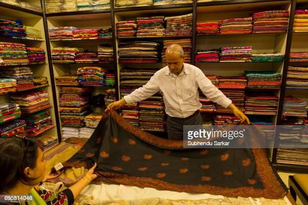 Kashmiri salesman shows a traditional shawl to a customer in a shop
