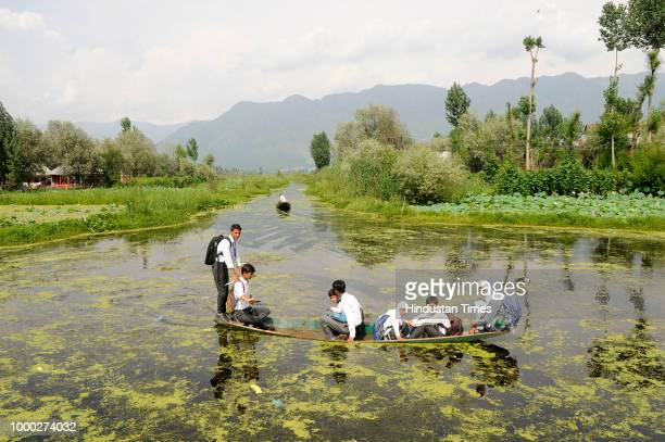 A flower vendor rows his boat in the waters of Nigeen Lake on July 16 2018 in Srinagar India