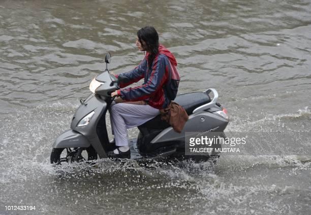 A Kashmiri school girl rides a scooter through a flooded street during a heavy rainfall in Srinagar on August 72018
