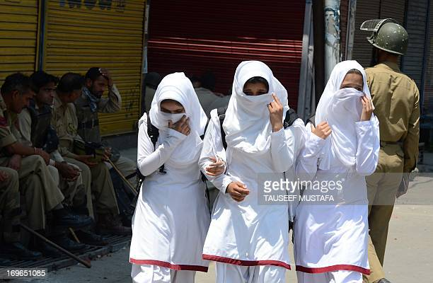 Kashmiri schoolgirls walk past Indian policemen as they conduct a patrol in Srinagar on May 30 2013 Every year thousands of tourists visit Kashmir...
