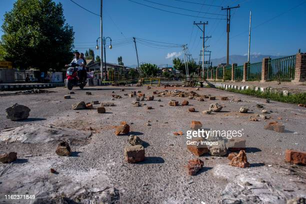 Kashmiri scooter rider travels past stones thrown by Kashmiri protesters at Indian forces which lie in the road in the Habba Kadal after a protest...