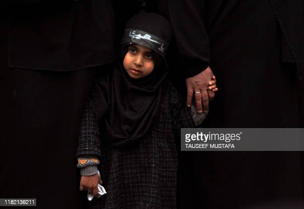 A Kashmiri Shiite girl holds her mothers hand as a Kashmiri Shiite Muslim flagellates himself with a cluster of knives during a Ashura procession in...