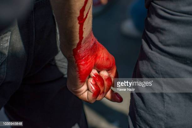 Kashmiri Shiite mourner's hand soked in his own blood as he flagellates himself during the Muharram procession on September 19 2018 in Srinagar the...