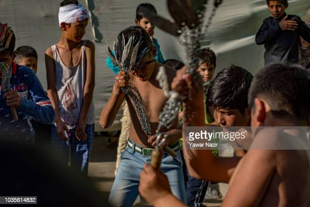 Kashmiri Shiite mourners walk barefoot and throw burning coal on Shiite mourners on the seventh day of Muharram on September 19 2018 in Khanda west...