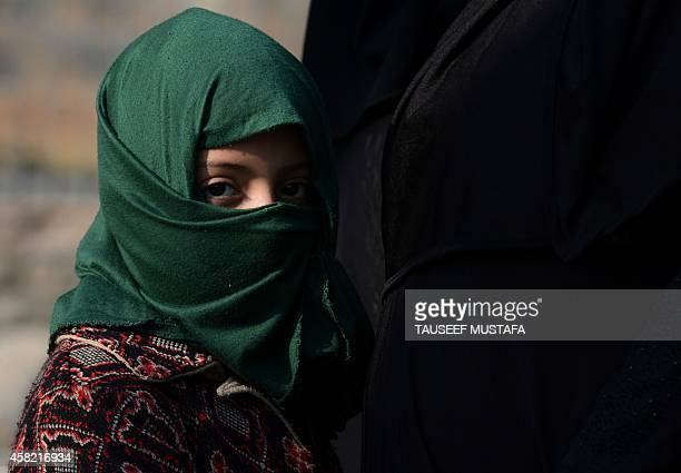 Kashmiri Shiite Muslim child looks on as devotees beat themselves with chains during a selfflagellation ritual at a religious procession held on the...