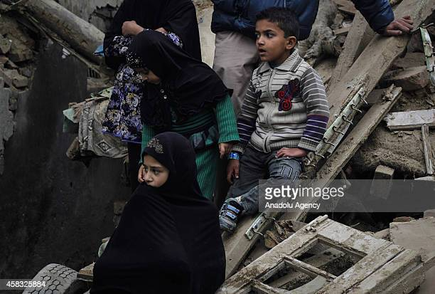 Kashmiri Shiite Muslim children sit on rubbles of a house which were damaged during floods in Kashmir as they watch ritual selfflagellation of...