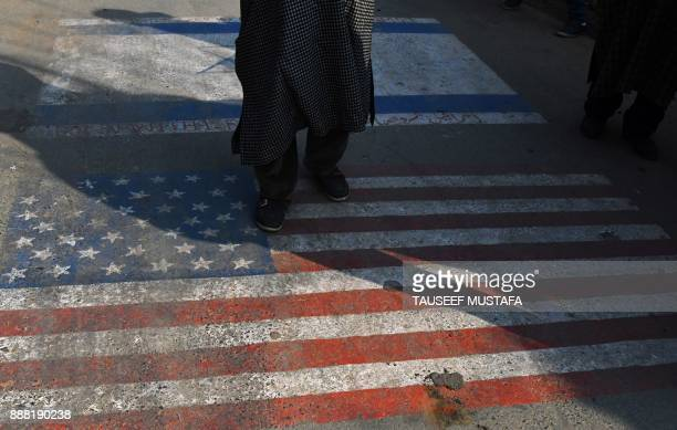 Kashmiri Shiite Muslim demonstrator stands on a United States flag painted on the streetduring a protest in Srinagar on December 8 following US...