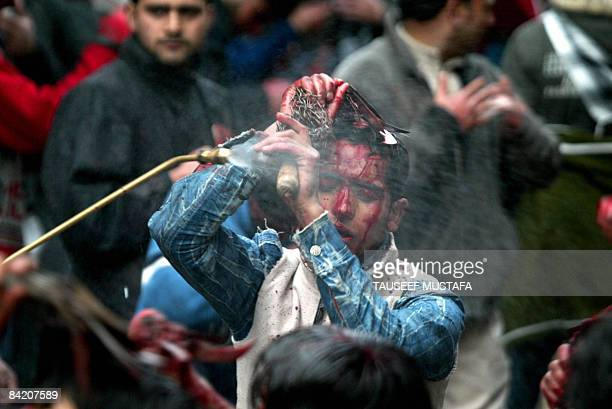 A Kashmiri Shiite Muslim flagellates himself with blades during a religious procession in observance of Ashura in Srinagar on January 8 2009 Ashura...