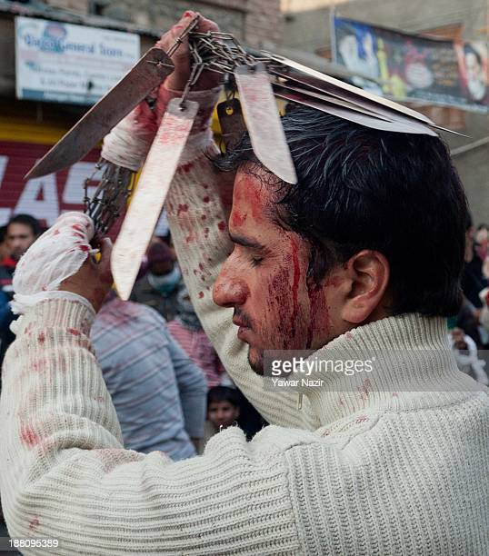 Kashmiri Shiite Muslim flagellates himself with sharp objects during an Ashura procession on November 15 in Srinagar the summer capital of Indian...