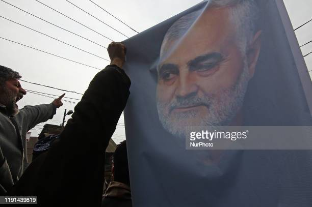 A Kashmiri Shiite muslim holds a picture of Iranian military General Qassem Soleimani as he marches during an antiAmerica protest in central Kashmir...