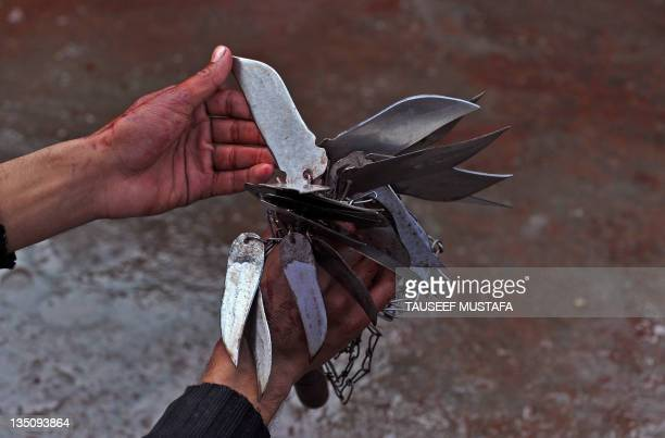 Kashmiri Shiite Muslim mourner holds blood soaked knives used in self flagelation during a religious procession in downtown Srinagar on December...