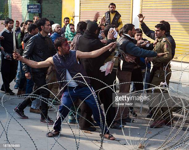 Kashmiri Shiite Muslim mourners clash with a police officer during a Muharram procession on November 13 2013 in Srinagar the summer capital of Indian...