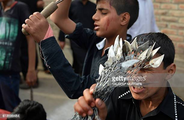 Kashmiri shiite muslim mourners flagellate themselves during a procession on the seventh day of Muharram in downtown Srinagar on October 9 2016...