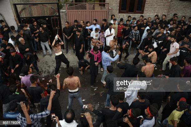 Kashmiri Shiite Muslim mourners flagellate themselves in a procession on the seventh day of Muharram in downtown Srinagar on September 28 2017 The...