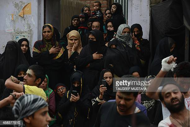 Kashmiri Shiite Muslim women look on as men perform a ritual of selfflagellation with knives during a religious procession in downtown Srinagar on...