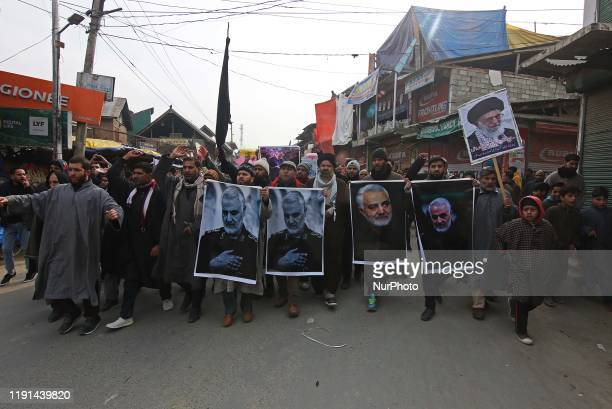 Kashmiri Shiite muslims carry pictures of killed Iranian general Qassem Soleimani as they march during an anti-America protest in central Kashmir on...