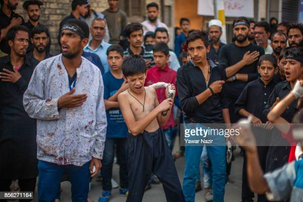 Kashmiri Shiite Muslims children flagella themselves with chains as they participate in an Ashura procession on October 1 in Srinagar the summer...