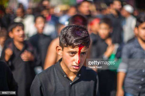 Kashmiri Shiite Muslims children smeared in blood participate in an Ashura procession on October 1 in Srinagar, the summer capital of Indian...