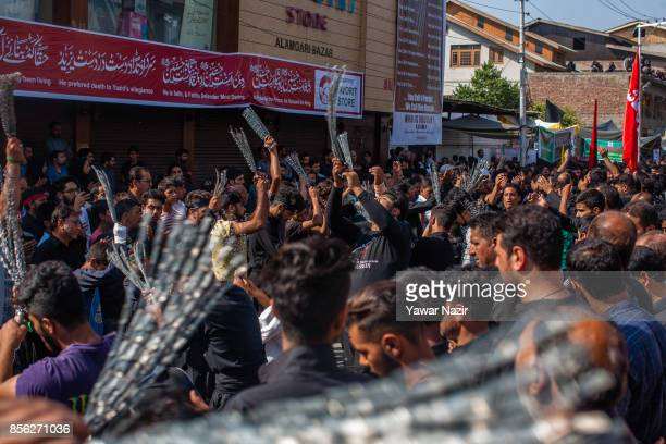 Kashmiri Shiite Muslims flagella themselves with chains as they participate in an Ashura procession on October 1 in Srinagar the summer capital of...