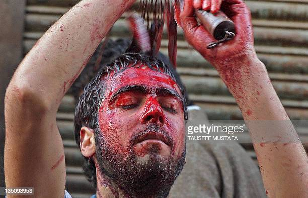 Kashmiri Shiite Muslims perform a ritual of self-flagellation with knives during a religious procession in downtown Srinagar on December 6,2011 held...