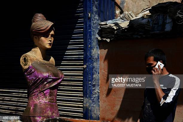 A Kashmiri shopkeeper talks on his mobile phone as he walks past a mudencrusted mannequin following flooding in central Srinagar on September 26 2014...