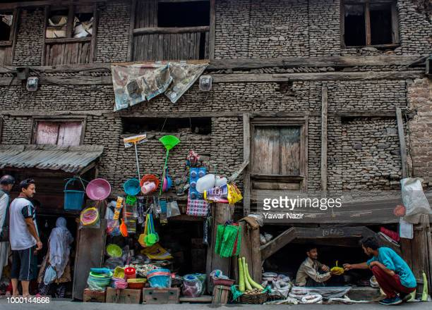 Kashmiri shopkeepers sell goods to customers in the basement of a dilapidated traditional house on July 16 2018 in Srinagar the summer capital of...