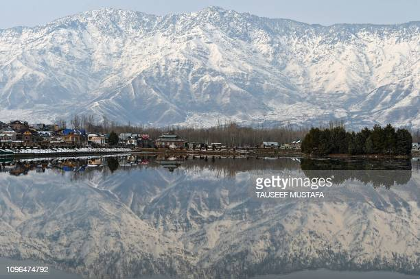 Kashmiri snowcovered mountains are reflected in Dal Lake in Srinagar on February 9 2019 Beause of recent heavy snowfalls the roads in Kashmir linking...
