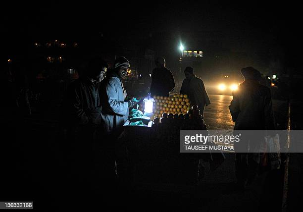 Kashmiri street vendor sells oranges under the light of a rechargeable lamp on a street in Srinagar on January 2, 2012. Security forces in Indian...