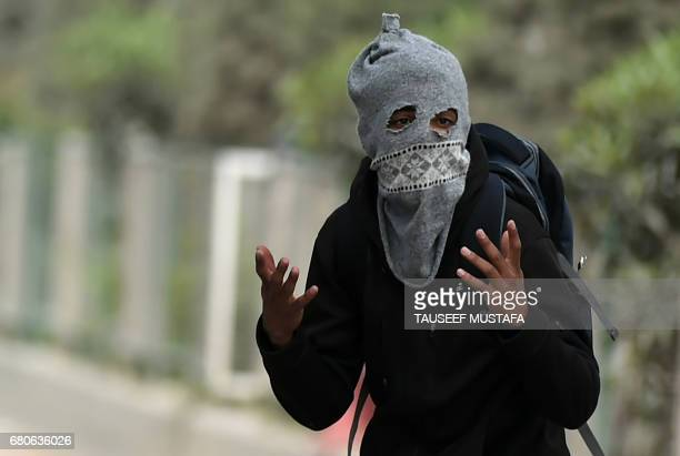Kashmiri student estures during clashes between students and Indian government forces in central Srinagar's Lal Chowk on May 9, 2017. Police fired...