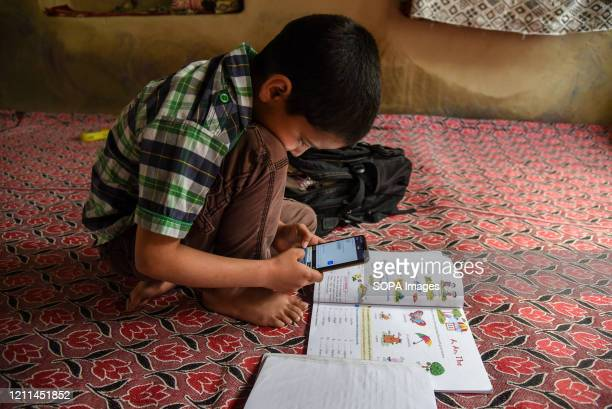 Kashmiri student listen to the lecture of his teacher during an online class via Zoom app as schools remain closed amid the fight against the...