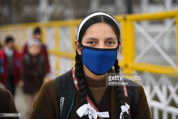 Kashmiri student wears a face mask as a protective measure against the corona virus Authorities in Kashmir order closure of all primary schools from...