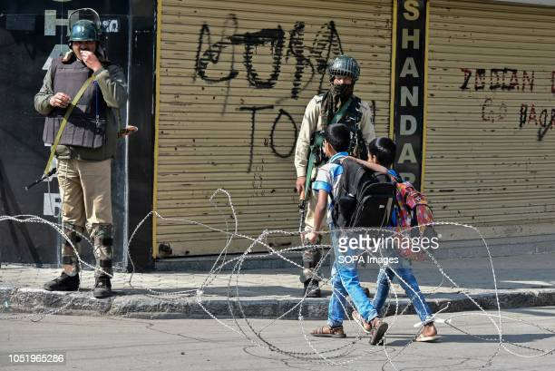 Kashmiri students walk past paramilitary troopers during restrictions in Srinagar Indian administered Kashmir Authorities impose restrictions in...