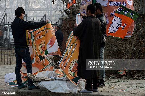 Kashmiri supporters of the Bharatiya Janata Party leader and Indian Prime Minister Narendra Modi hang banners bearing their images in Srinagar on...