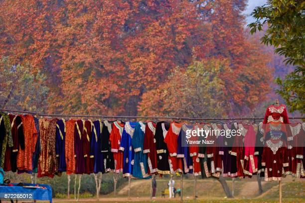 Kashmiri traditional dresses are hanged by photographers on a road to attract tourists in the Nishat Mughal garden during the autumn season on...