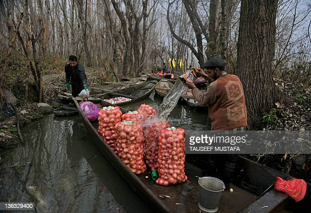 Kashmiri turnip farmers clean their harvest in sacks, as they prepare to travel to a floating vegetable market on Dal Lake in Srinagar on January 2,...