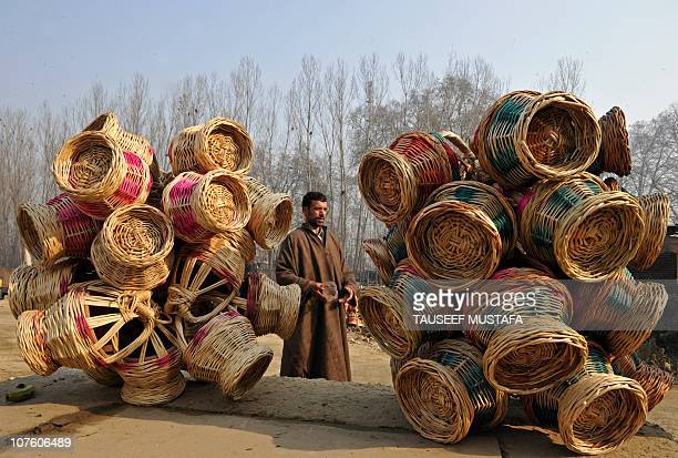 A Kashmiri vendor arranges Kangir traditional Kashmiri fire pots at a market in Srinagar on December 8 2010 With the arrival of winter in the Kashmir...