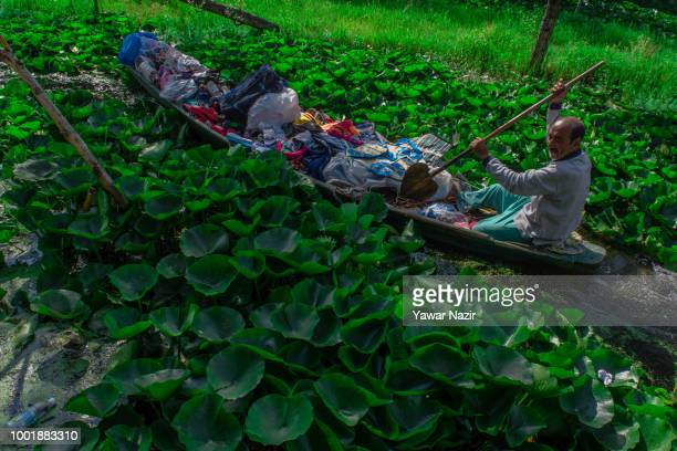 Kashmiri vendor ferrying goods rows his boat amid water lilies on Dal lake on July 19 2018 in Srinagar the summer capital of Indian administered...