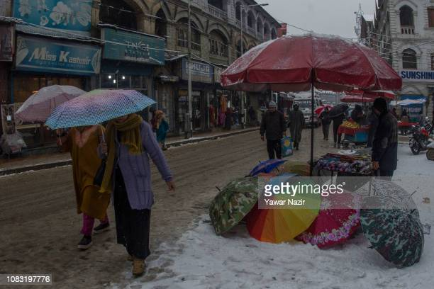A Kashmiri vendor sells umbrellas on a roadside amid fresh snowfall on January 16 2019 in Srinagar the summer capital of Indian administered Kashmir...