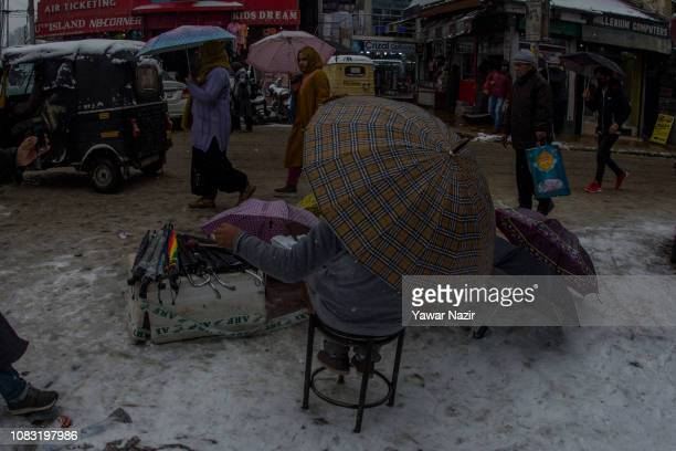 Kashmiri vendor sells umbrellas on a roadside amid fresh snowfall on January 16 2019 in Srinagar the summer capital of Indian administered Kashmir...