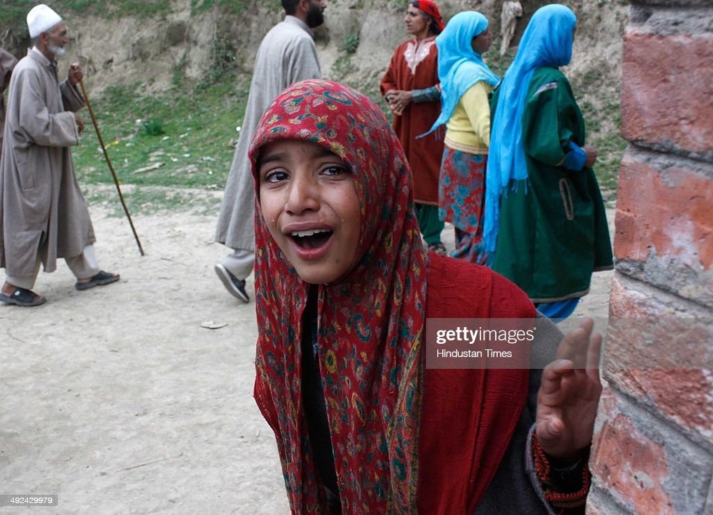 A Kashmiri village girl crying during the funeral procession of an Army soldier Mushtaq Ahmad Mir at Qazipora Chadoora district, on May 20, 2014 in Srinagar, India. Mushtaq Ahmad Mir, an Army soldier who was killed in an encounter at Chadoora yesterday. An Army soldier was killed and three others injured in an ongoing encounter at Chadoora in district Budgam of central Kashmir. Sources said that militants managed their escape from the spot and forces were now extending the cordon to more areas.