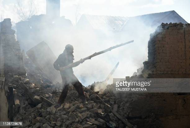A Kashmiri villager clears debris of house destroyed during a deadly gun battle between militants and Indian government forces in Tral area of...